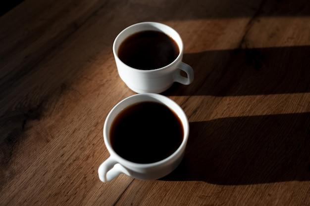 나무 테이블에 그림자와 함께 커피의 두 개의 흰색 세라믹 컵의 근접 촬영.