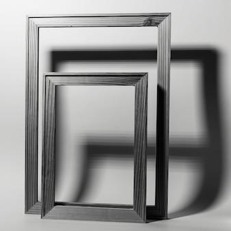 회색 배경에 그림자와 함께 두 개의 나무 프레임의 근접 촬영. 흑백 사진.