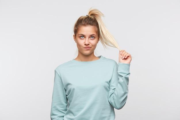 금발 머리와 포니 테일을 가진 불행한 예쁜 젊은 여자의 근접 촬영은 파란색 셔츠를 입는다.