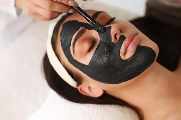 フェイスマスクを適用している認識できない美容師のクローズアップ