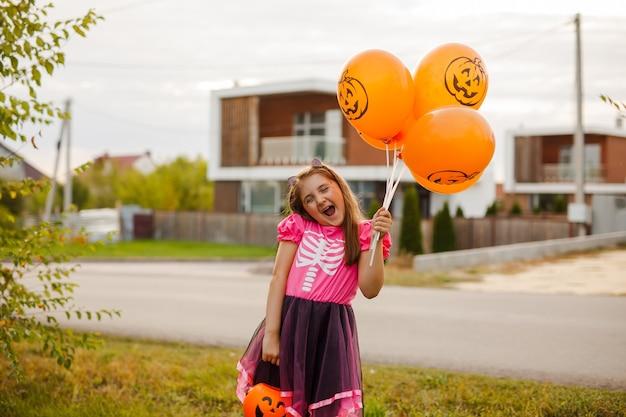 ハロウィーンの衣装を着て笑い、トリックオアトリートシーズンにカボチャのバスケットを持っている認識できない少女のクローズアップ、コピースペース