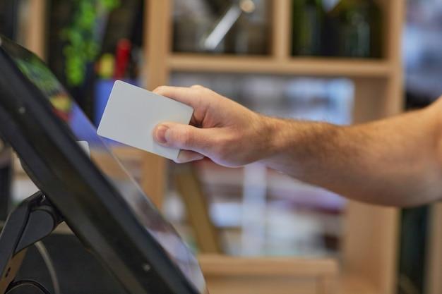 注文と支払いを処理している間、カフェでレジスターコンピュータを使用して認識できない男のクローズアップ、コピースペース