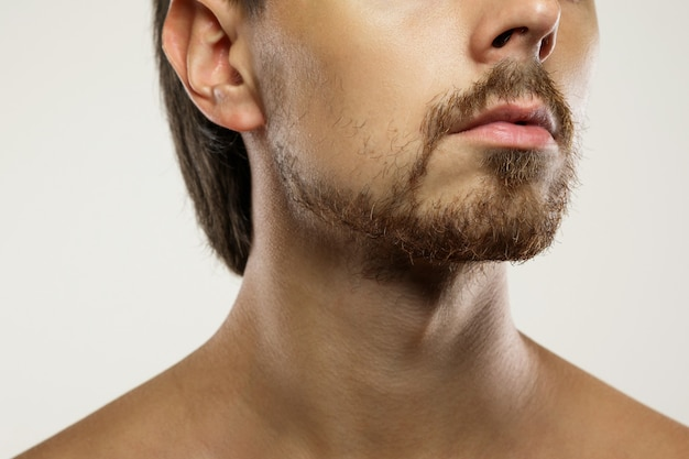 깔끔한 수염을 가진 면도되지 않은 남자의 얼굴의 근접 촬영