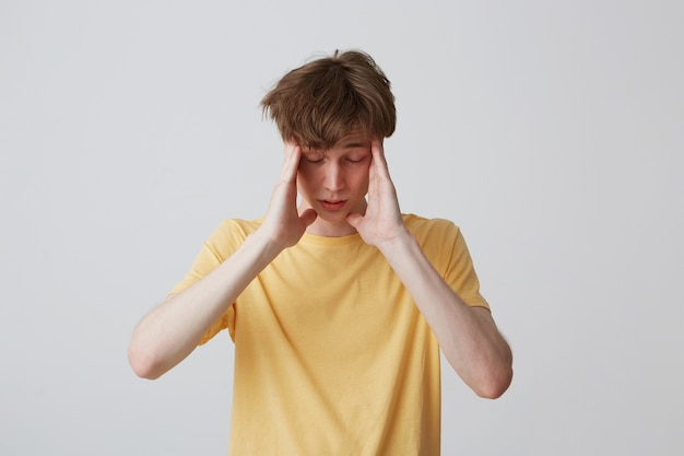 黄色のtシャツで動揺して落ち込んでいる若い男のクローズアップ