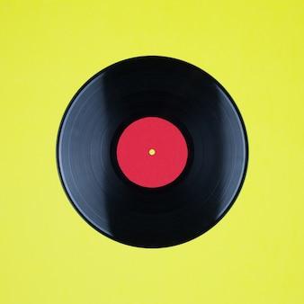 黄色の壁にコピースペース付きのラベルが付いたビニールロングプレイレコードのクローズアップ