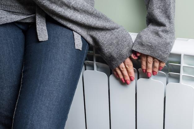 Крупным планом потепления замерзшей женщины возле радиатора