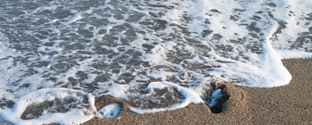여름의 화창한 날에 해변 모래에 파도의 근접 촬영. 고품질 사진