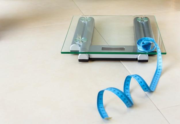 バスルームの体重計と青い巻尺のクローズアップ。健康とダイエットの概念。