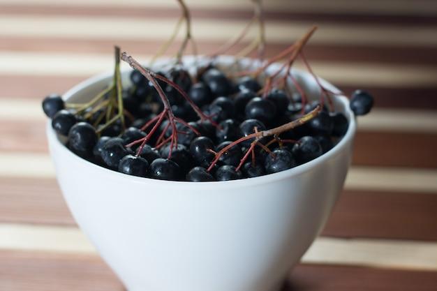 Крупным планом влажные ягоды аронии в белой простой миске на деревянном столе