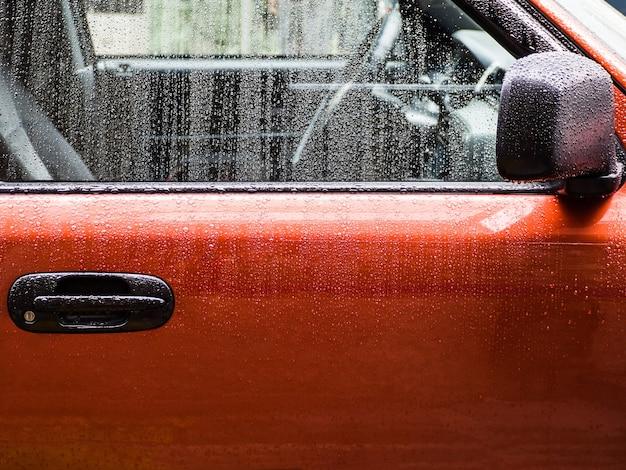 비 후 물에 젖은 빨간 차의 근접 촬영