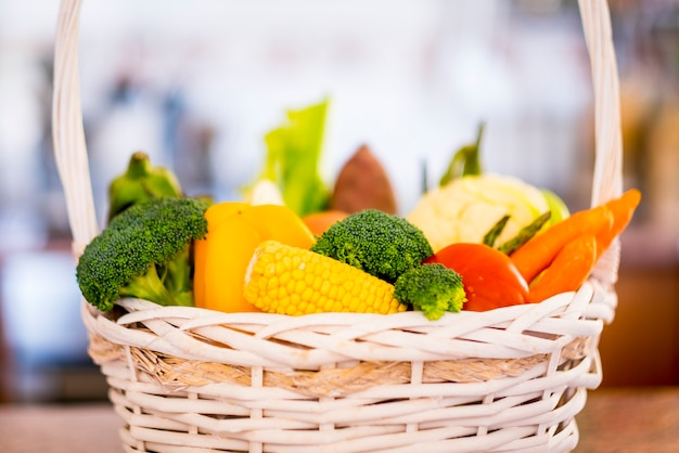 さまざまな種類の新鮮な生野菜でいっぱいの白いバスケットのクローズアップ健康的な食事の概念