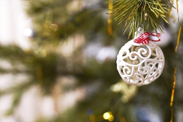 장식된 크리스마스 트리에서 매달려 흰색 값싼 물건의 근접 촬영. 레트로 필터 효과입니다.