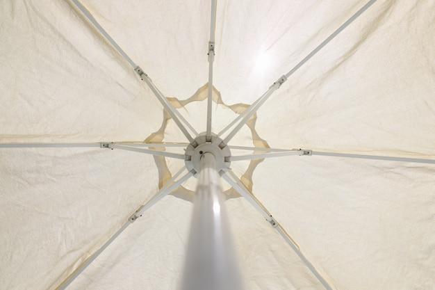 Крупным планом белый пляжный зонт снизу