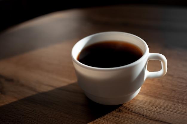 나무 테이블에 커피의 흰색 세라믹 컵의 근접 촬영.