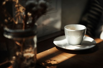 Closeup of white coffee cup on wooden table
