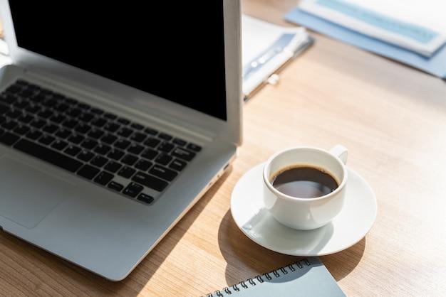 コンピューターのラップトップ、ノートブック、紙クリップボードと木製の作業テーブル上のブラックコーヒーの白いカップのクローズアップ。