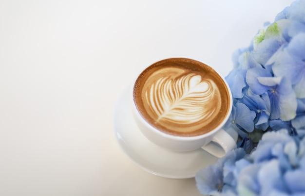 青と紫のアジサイの花と白いテーブルにミルクフォームハート形のアートとホットコーヒーカフェラテの白いカップのクローズアップ。