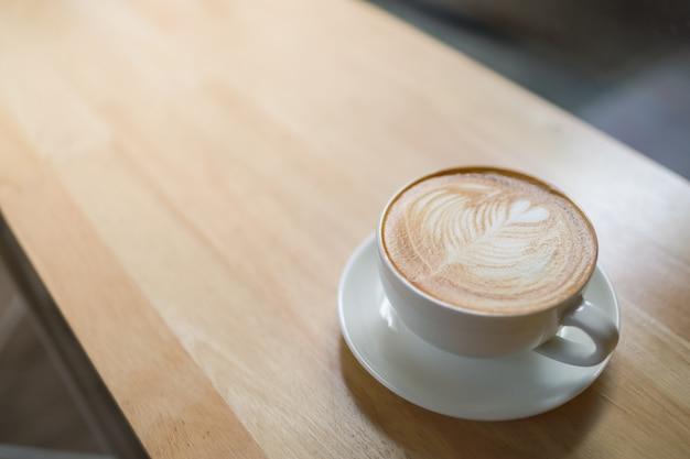 Крупный план белой чашки горячего latte кофе с искусством формы сердца пены молока на деревянном столе под солнечным светом утра и космосом тени и экземпляра.