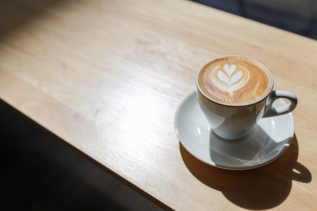 Крупный план белой чашки горячего latte кофе с искусством формы сердца пены молока на деревянном столе под солнечным светом и тенью утра.