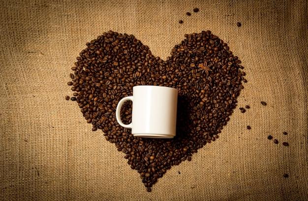 コーヒー豆で作ったハートの真ん中に白いマグカップのクローズアップ