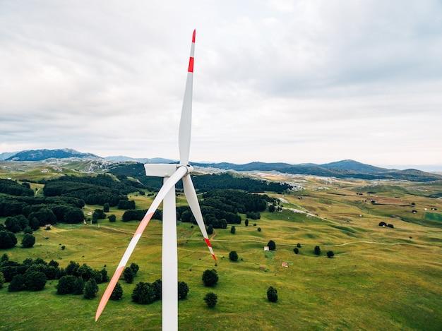 녹색 숲과 들판에 빨간 줄무늬가있는 풍력 터빈 블레이드의 근접 촬영