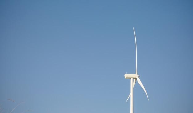 푸른 하늘 배경 위에 전기를 생성하는 풍차 터빈과 블레이드의 근접 촬영. 깨끗하고 생태학적인 에너지 생산 개념입니다.