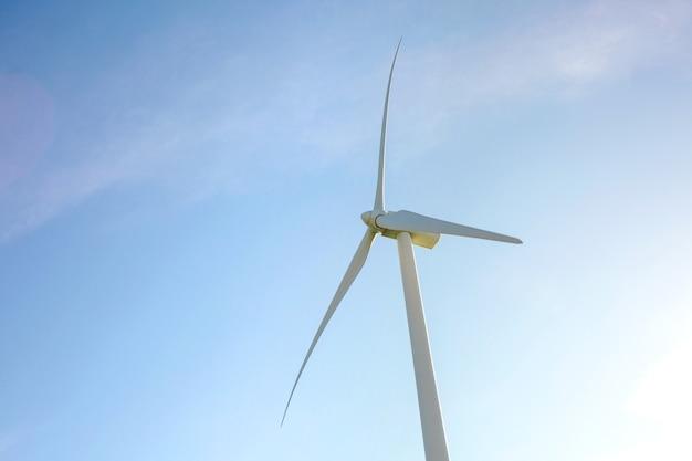 푸른 하늘 위에 전기를 생성하는 풍차 터빈과 블레이드의 근접 촬영. 깨끗하고 생태학적인 에너지 생산 개념입니다.