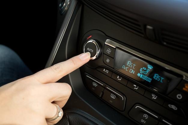 車の気候制御システムで温度を調整する女性のクローズアップ