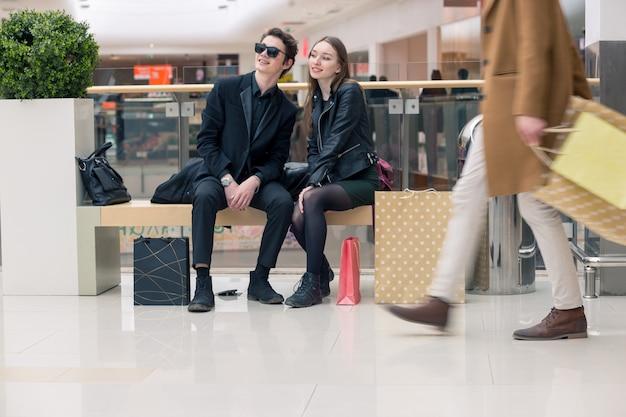 カラフルな買い物袋でベンチに女と男のクローズアップ