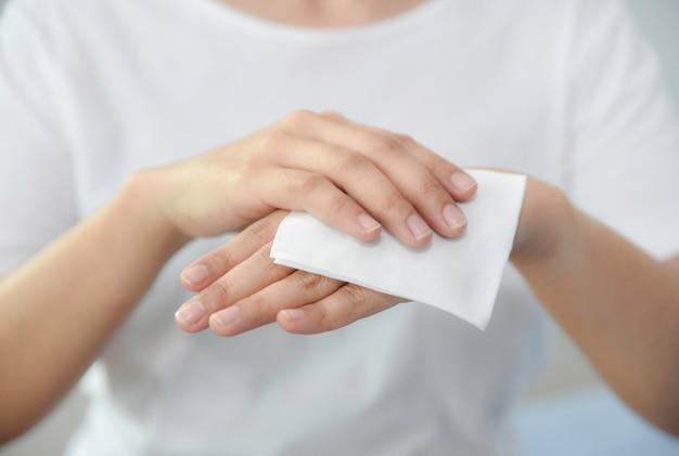 Крупный план женщины очищая ее руки с тканью. здравоохранение и медицинская концепция.