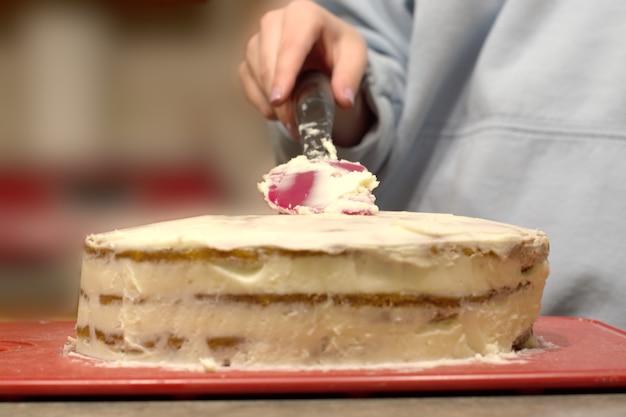 Крупный план женщины, украшающей торт на кухне, концепция еды и людей