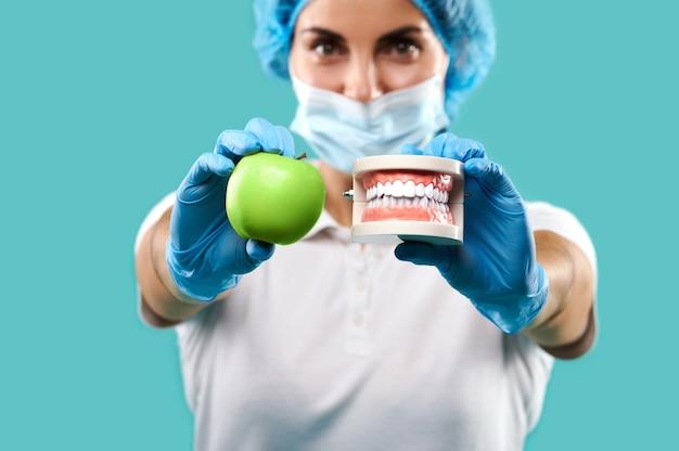Крупным планом женщина-дантист держит зеленое яблоко в одной руке и челюсть в другой и показывает их на камеру. синий фон