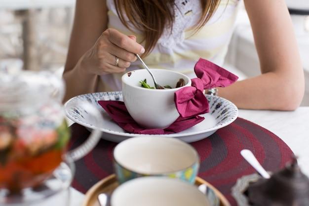 カフェでチョコレートケーキを食べる女性のクローズアップ
