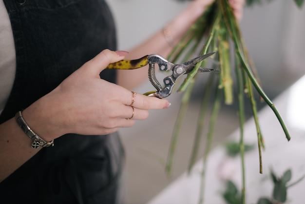 흰색 바탕에 가위로 꽃 줄기를 자르는 여성 꽃집 손 클로즈업