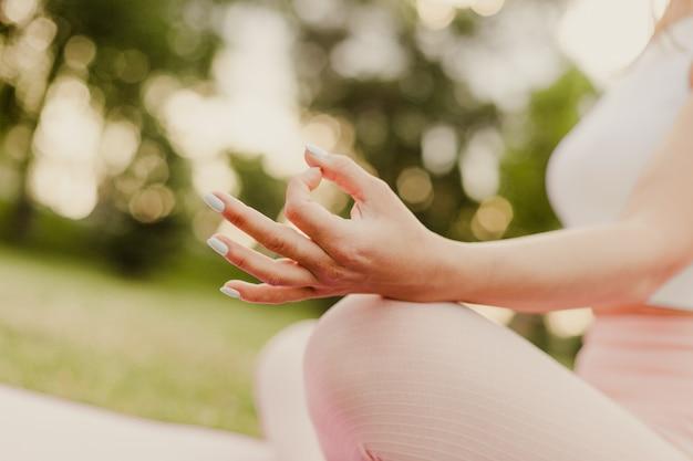 呼吸とリラクゼーションの蓮華座の概念を瞑想する女性の手のクローズアップ