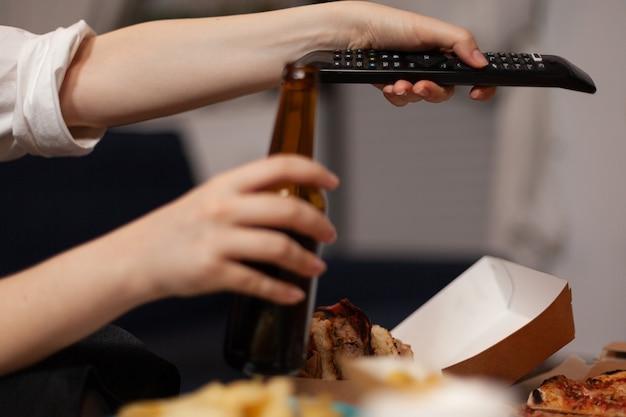 Крупным планом руки женщины меняют каналы с помощью удаленного просмотра развлекательного комедийного фильма Бесплатные Фотографии