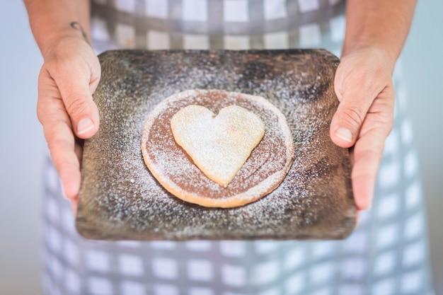 女性の手のクローズアップは、記念日やイベントのために準備された小さなケーキを示しています-キッチンで自家製のチョコレートと天然成分を使用した地球のデザイン-ビューの上においしい料理