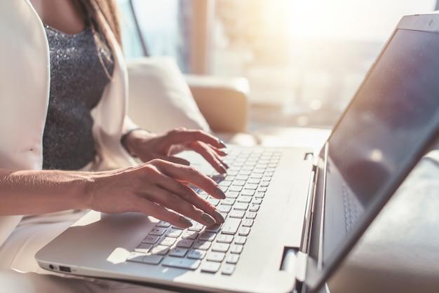 ノートパソコンのキーボードで入力する女性の手のクローズアップ。