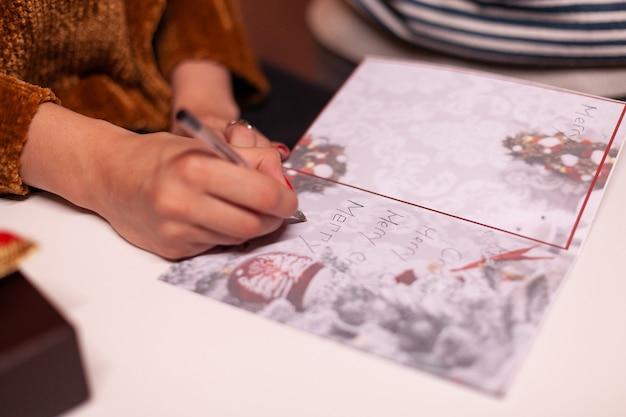 クリスマス休暇中に家族のためのクリスマスグリーティングカードを書く女性の手のクローズアップ