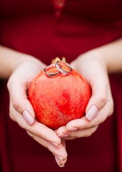結婚指輪とザクロを保持している女性のクローズアップ