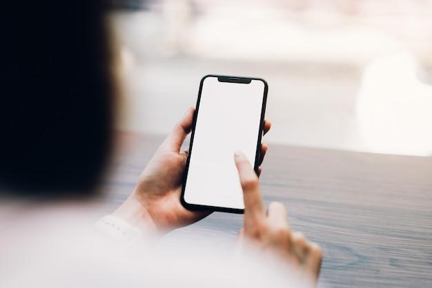 スマートフォンを保持している女性のクローズアップ、空白の画面のモックアップ。カフェで携帯電話を使用しています。