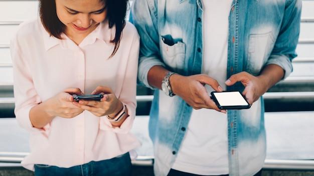 スマートフォンを保持している女性のクローズアップ、空白の画面のモックアップ。ライフスタイルに携帯電話を使用しています。通信概念のための技術