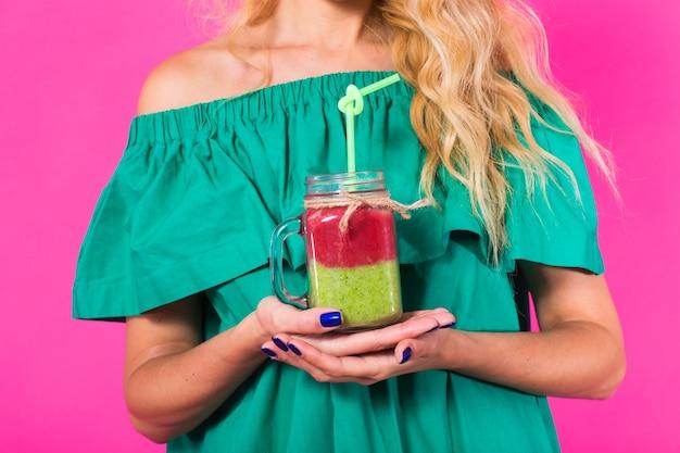 ピンクの壁においしい緑のスムージーミルクセーキを保持し、飲んでいる女性のクローズアップ