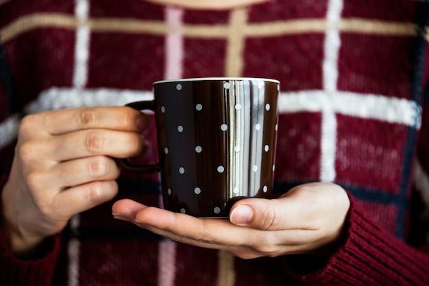 Крупным планом женщина с чашкой горячего напитка