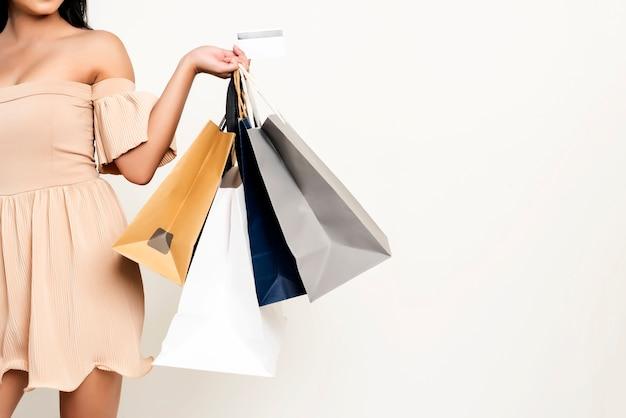 買い物袋とクレディを持っている女性のクローズアップ Premium写真