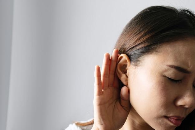 女性のクローズアップは耳の近くで彼女の手を握り、灰色の背景で注意深く耳を傾けます。聴覚障害、聴覚障害の概念。
