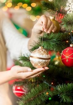 つまらないものでクリスマスツリーを飾るセーターの女性のクローズアップ
