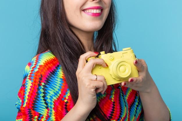 Крупным планом женщина держит в руках желтую винтажную модель камеры, позирующую на синей поверхности