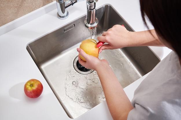 Крупным планом женщина пилинг яблоко над раковиной в кухне