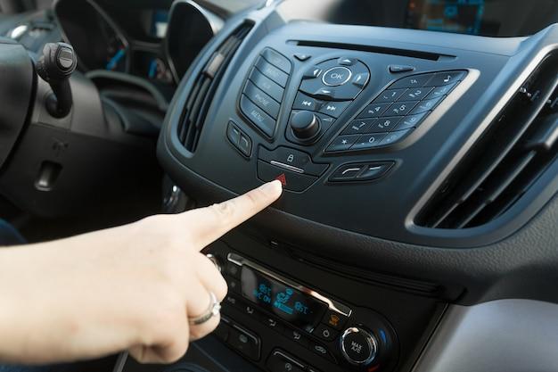 赤い車の緊急ボタンを押す女性のクローズアップ